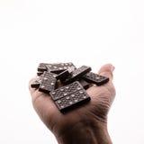Domino's in een vrouwelijke hand, witte achtergrond Stock Afbeeldingen