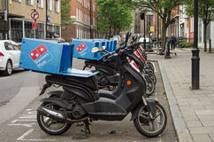 Domino's Pizza Mopeds, London. LONDON, ENGLAND - MAY 17, 2014: A row of mopeds operating for the Domino's Pizza takeaway chain parked in Westminster, London Royalty Free Stock Photography