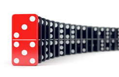 Domino tiles in a row. Unique red domino tile and many black dominoes. Leadership, individuality and difference concept Royalty Free Stock Photos