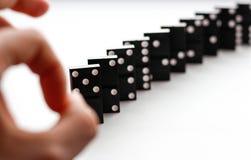 Dominobricka knackar knäppet av ett finger Domino som isoleras på en whit Arkivfoton