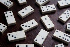 Dominobrickastycken på de bruna trätabellbakgrundslekarna lyckas förmögenhet Royaltyfri Bild