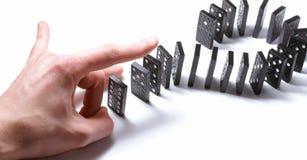 Dominoe Stücke gedrückt durch eine menschliche Hand Stockfotos
