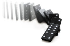 Dominoeffect with falling black dominos on a white background. Domino effect with falling black dominoes on a white background, selective focus and very narrow Stock Image