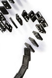 Dominoes. A stack of black dominoes falling on white background Stock Photography