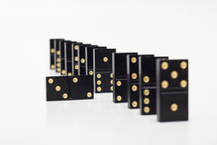 Dominoes. One domino piece is fallen from row Royalty Free Stock Photos