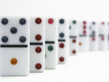 Dominoes. With colorful dots standing in a line showing depth of field Royalty Free Stock Photo