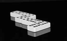 Dominoes on black shining surface Royalty Free Stock Photos
