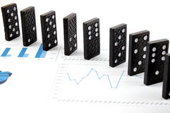 Dominoes on chart Stock Images