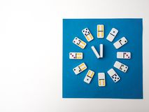 Dominoes clock  on white blue background. Time to play Stock Photography