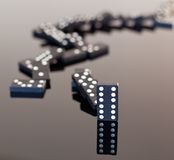 Dominoes collapsed on reflective surface Stock Image