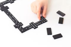 Dominoes game, Kids hand is holding a domino tile. Dominoes game. Kids hand is holding a domino tile with some on table. Boardgame concept stock images