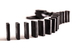 Dominoes in a line. Black dominoes in a curved line ready to topple, on a white background Stock Photography
