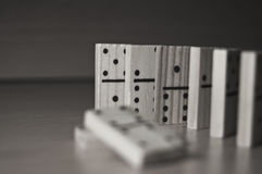 Dominoes in monochrome. A closeup of domino tiles being placed upright in a row, with 2 toppled ones out of focus in the foreground. Picture in black and white Stock Image