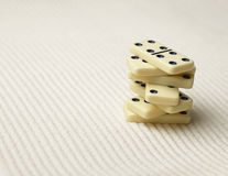 Dominoes pile on surface of sand Stock Images