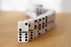 Dominoes snake. A snaking line of dominoes, focus on front brick stock image