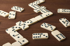 Dominoes on a wooden table. The game is tabletop. Dark background stock images