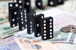 Dominos debout sur des billets de banque Images libres de droits