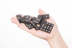 Dominos in der weiblichen Hand auf einem weißen Hintergrund Stockbilder
