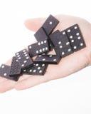 Dominos in der weiblichen Hand auf einem weißen Hintergrund Lizenzfreies Stockfoto