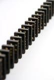 Dominos noirs restant dans la ligne Photographie stock libre de droits