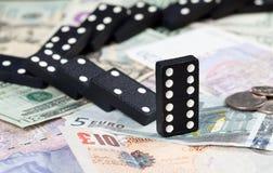 Dominos tombés sur des billets de banque Images stock