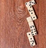 Dominostücke auf dem braunen Holztischhintergrund Lizenzfreies Stockfoto