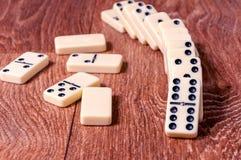 Dominostücke auf dem braunen Holztischhintergrund Lizenzfreies Stockbild