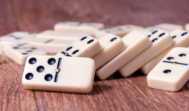 Dominostücke auf dem braunen Holztischhintergrund Stockfotos
