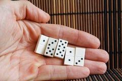 Dominostukken in mensen` s hand, op de houten achtergrond van de bamboe bruine lijst Stock Foto's