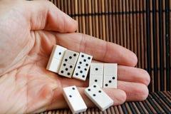 Dominostukken in mensen` s hand, op de houten achtergrond van de bamboe bruine lijst Royalty-vrije Stock Afbeeldingen