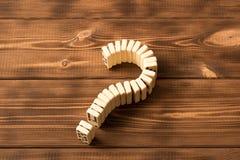 Dominovraagteken op houten lijst Dominoprincipe stock foto