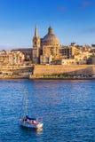 Domkyrka för Valletta Malta - StPaul ` s i guld- timme på huvudstaden Valletta för Malta ` s med segelbåten royaltyfria foton