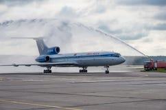 Domodedovo-Flughafen, Moskau - 11. Juli 2015: Tupolev Tu-154M EW-85748 von Belavia-Fluglinien gegrüßt durch Wasserbogen Stockbild