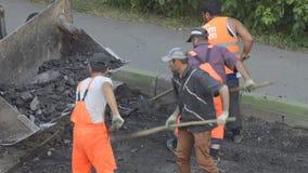 DOMODEDOVO, RÚSSIA - 17 DE MAIO DE 2017: Os trabalhadores da estrada carregam partes de asfalto velho em uma cubeta da escavadora filme