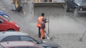 DOMODEDOVO, RÚSSIA - 17 DE MAIO DE 2017: Os trabalhadores da estrada carregam partes de asfalto velho em uma cubeta da escavadora video estoque