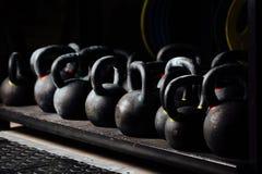 Domoor voor gewichtheffen in gymnastiek Zwarte kettlebells 24kg Stock Foto's