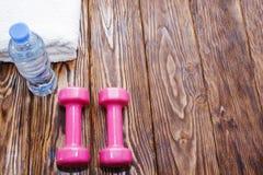 Domoren en een fles water met handdoek op houten achtergrond, concept die aan de hoogste mening van de geschiktheidssportuitrusti royalty-vrije stock foto