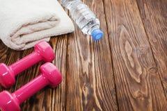 Domoren en een fles water met handdoek op houten achtergrond, concept die aan de hoogste mening van de geschiktheidssportuitrusti stock foto's