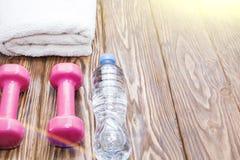 Domoren en een fles water met handdoek op houten achtergrond, concept die aan de hoogste mening van de geschiktheidssportuitrusti stock afbeelding