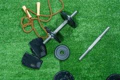 Domoren, gewichtsschijven, handschoenen en toebehoren voor sport, op het gras, Fitness royalty-vrije stock afbeeldingen