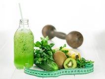 Domorengeschiktheid en fles van komkommer smoothies op witte houten lijst Stock Afbeeldingen
