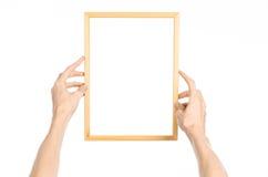 Domowa dekoracja i fotografia Ramowy temat: ludzka ręka trzyma drewnianą obrazek ramę odizolowywająca na białym tle w pracowniane Fotografia Royalty Free