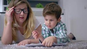Domowa edukacja, mum z syna remisu obrazkami z barwionymi markierami na bielu prześcieradła lying on the beach na podłoga w domu zbiory