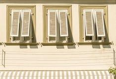 Domowa fasada z stiuku 3 okno aw i wyjawionymi drewnianymi żaluzjami zdjęcie royalty free