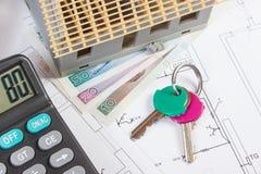 Domowa w budowie, klucze, kalkulator i połysk waluta na elektrycznych rysunkach, pojęcie budynku dom Zdjęcie Royalty Free