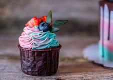 Domowej roboty babeczki z różową i turkusową śmietanką, dekorującą z truskawkami i czarnymi jagodami Obrazy Royalty Free