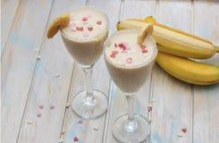 Domowej roboty Bananowi smoothies lub koktajl na drewno stole zdjęcie stock
