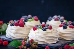 Domowej roboty bezy podstawa dla tortowego Pavlova z świeżymi czarnymi jagodami i cukierem na czarnym tle jeżynowym i sproszkowan Obraz Stock