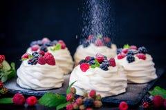Domowej roboty bezy podstawa dla tortowego Pavlova z świeżymi czarnymi jagodami i cukierem na czarnym tle jeżynowym i sproszkowan Fotografia Royalty Free