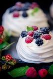 Domowej roboty bezy podstawa dla tortowego Pavlova z świeżymi czarnymi jagodami i cukierem na czarnym tle jeżynowym i sproszkowan Obrazy Stock